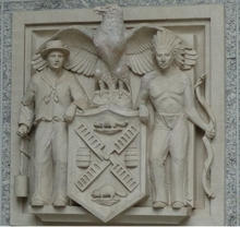 This coat of arms refers to early times of Manhattan, when its name was still New Amsterdam.Arms are carved on an entrance of one of the City Hall buildings.(Photo: RTJLWL, 2015)